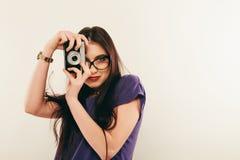 Junge lächelnde Frau, die ein Foto durch alte Fotokamera macht photograph lizenzfreies stockfoto