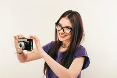 Junge lächelnde Frau, die ein Foto durch alte Fotokamera macht photograph lizenzfreie stockbilder