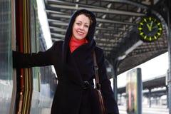 Junge lächelnde Frau, die geht, eine Serie zu betreten. Stockbild