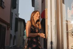 Junge lächelnde Frau, die Geschäftsfenster in einer Gasse im ascona betrachtet lizenzfreie stockfotografie