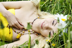 Junge lächelnde Frau, die im Gras stillsteht. Lizenzfreies Stockbild