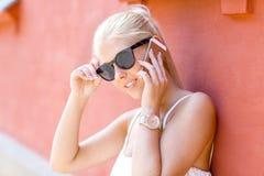 Junge lächelnde Frau, die im Telefon im Freien spricht Stockfotografie