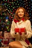 Junge lächelnde Frau, die rotes Weihnachtsgeschenk anhält Stockfotos