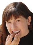 Junge lächelnde Frau, die Schokolade isst Stockfotos