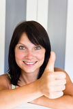 Junge lächelnde Frau, die sich Daumen zeigt Lizenzfreie Stockfotos