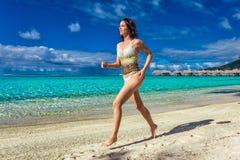 Junge lächelnde Frau, die Spaß auf dem tropischen Strand hat stockbilder