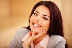 Junge lächelnde Frau, die am Tisch sitzt Stockfoto
