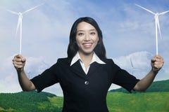 Junge lächelnde Frau, die zu den Windkraftanlagen hält und Kamera betrachtet Stockfotografie