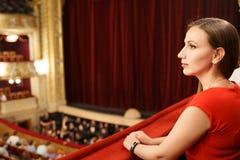 Junge lächelnde Frau im Kleid, das im Theater sitzt Lizenzfreie Stockfotografie