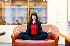 Junge lächelnde Frau meditiert auf dem Sofa im Büro lizenzfreie stockbilder