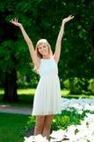 Junge lächelnde Frau mit den Armen draußen angehoben Stockfotografie