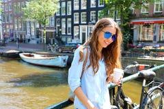 Junge lächelnde Frau mit der Sonnenbrille, die Kaffeetasse nahe ihrem Fahrrad in ihrer Abschaltzeit beim Warten auf jemand in Ams Stockfotografie