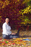 Junge lächelnde Frau mit Laptop Lizenzfreies Stockfoto