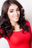 Junge lächelnde Frau mit rotem Kleid des langen gelockten braunen Haares Stockfotografie