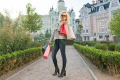 Junge lächelnde Frau mit Taschen für den Einkauf, sonniger Stadthintergrund, goldene Stunde lizenzfreie stockbilder