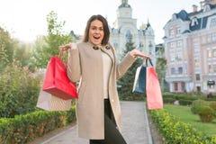 Junge lächelnde Frau mit Taschen für den Einkauf, sonniger Stadthintergrund, goldene Stunde lizenzfreies stockfoto