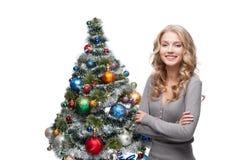 Junge lächelnde Frau nahe Weihnachtsbaum Stockfotos