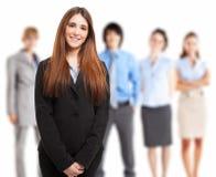 Junge lächelnde Frau vor einer Gruppe von Personen Lizenzfreie Stockfotos
