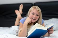 Junge lächelnde Frau, wie sie ein Buch liest Stockfotos