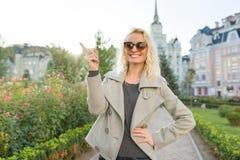 Junge lächelnde Frau zeigt sich Zeigefinger, Aufmerksamkeitsidee Eureka, Hintergrund im Freien, goldene Stunde stockfotografie