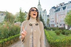 Junge lächelnde Frau zeigt sich Zeigefinger, Aufmerksamkeitsidee Eureka, Hintergrund im Freien, goldene Stunde stockfotos