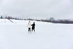 Junge lächelnde Frauen auf Eisbahnrückseite lizenzfreies stockbild