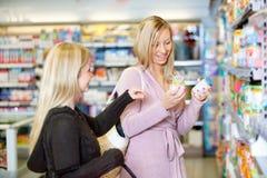 Junge lächelnde Frauen beim zusammen kaufen stockbild