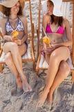 Junge lächelnde Frauen, die exotische Cocktails anhalten Lizenzfreie Stockfotografie