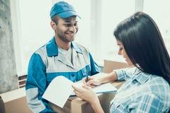Junge lächelnde Frauen-unterzeichnende Form für Lieferung lizenzfreies stockfoto