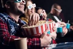 junge lächelnde Freunde in den Gläsern 3d Popcorn essend und Film aufpassend lizenzfreies stockfoto