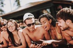 Junge lächelnde Freunde, die Smartphone am Poolside verwenden lizenzfreies stockbild