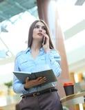 Junge lächelnde Geschäftsfrau, die telefonisch, Tagebuch im Büro halten spricht stockfotos