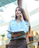 Junge lächelnde Geschäftsfrau, die telefonisch, Tagebuch im Büro halten spricht lizenzfreies stockfoto