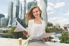 Junge lächelnde Geschäftsfrau mit Haufen von Papieren Lizenzfreie Stockfotos