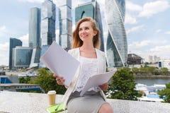 Junge lächelnde Geschäftsfrau mit Haufen von Papieren Stockfotografie