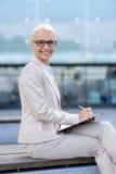 Junge lächelnde Geschäftsfrau mit Notizblock draußen Stockfoto