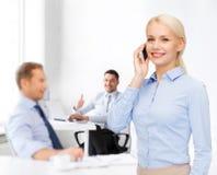 Junge lächelnde Geschäftsfrau mit Smartphone Lizenzfreie Stockbilder