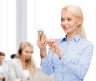 Junge lächelnde Geschäftsfrau mit Smartphone Stockfotografie