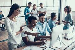 Junge lächelnde Geschäftsleute, die im Büro arbeiten lizenzfreie stockfotografie