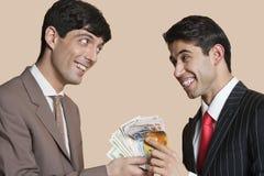 Junge lächelnde Geschäftsmänner beim einander mit Euros in der Hand betrachten Stockfoto