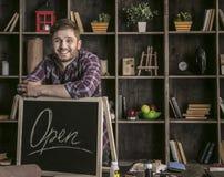 Junge lächelnde lederne Arbeitskraft des Mannes, die bei Tisch nahe offenem Zeichen mit Werkzeugen steht Stockfotos