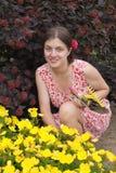 Junge lächelnde Mädchenblumenhändler, die im Garten arbeiten Stockbild