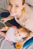 Junge lächelnde Mutter bei der Fütterung einer kleinen Tochter mit Säuglingsnahrung Stockbilder