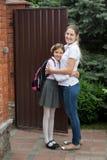 Junge lächelnde Mutter, die weg von ihrer Tochter zur Schule sieht Stockbilder