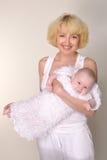 Junge lächelnde Mutter hält ihr Schätzchen in den Armen an stockbild