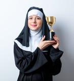 Junge lächelnde Nonne mit goldener Trophäenschale Stockbilder