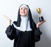 Junge lächelnde Nonne mit goldener Trophäenschale Lizenzfreies Stockbild