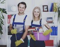 Junge lächelnde Paare halten Reinigungswerkzeuge stockfotos