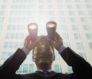 Junge, lächelnde stehende Außenseite des Geschäftsmannes eines Wolkenkratzers und des Schauens durch Ferngläser mit Blendenfleck i Lizenzfreie Stockbilder