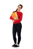 Junge lächelnde Studentenfrau, die Bücher hält lizenzfreie stockfotografie